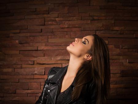 updo: Stylish woman with leather jacket standing near brick wall