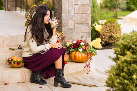 Pretty woman sitting on a porch decorated for Thanksgiving and Halloween