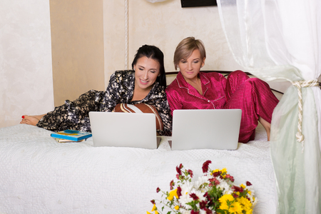 Two pretty friends sitting at the laptops early in the morning