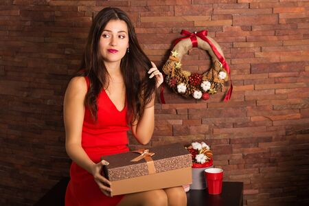 Woman in red dress opening Christmas present