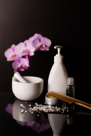Cosmetics essential with a beautiful orchid on a black backdrop