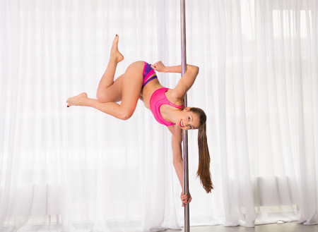 Pretty pole dancer woman in the studio