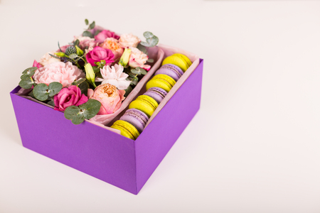 Beautiful flowers and a gift box with macaron cookies