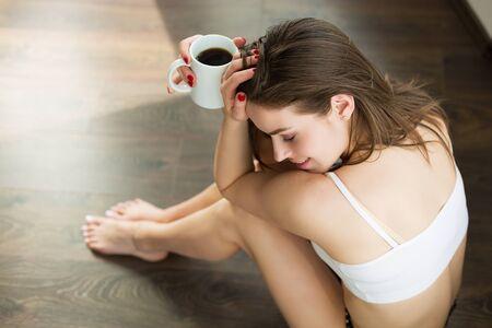 Beautiful woman having coffee early in the morning
