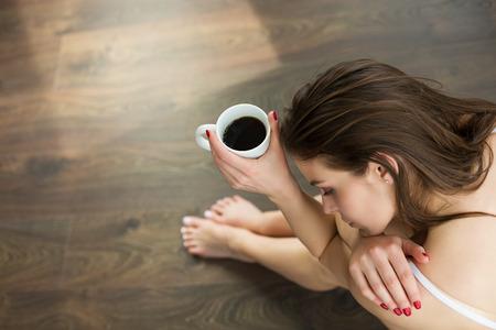 Woman enjoyin a cup of coffee early in the morning