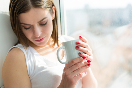 early twenties: Woman drinking coffee in the morning sitting by the window