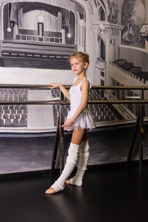 gaiters: Little ballerina in a white dress in a dance studio Stock Photo