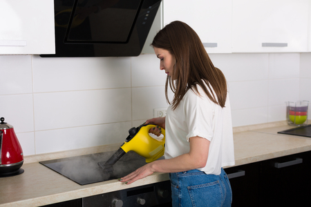Young beautiful woman cleaning kitchen with steam cleaner