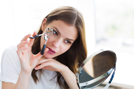 Woman sitting by the mirror and applying makeup