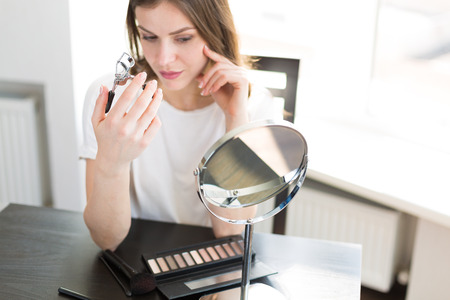 Woman applying make up sitting by the mirror