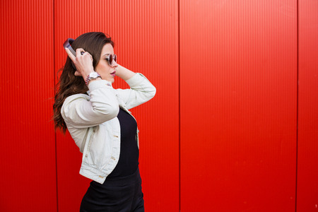 all ok: Stylish young woman standing near the red wall Stock Photo