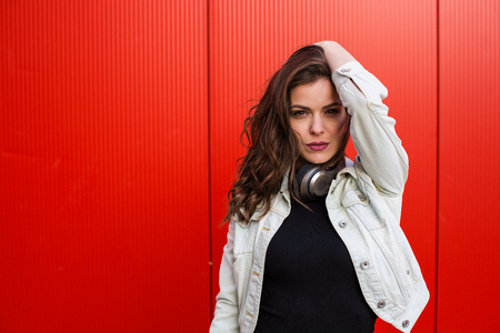Stylish young woman standing near the red wall Stock Photo