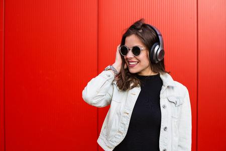 赤い壁の近くに立ってスタイリッシュな若い女性 写真素材 - 78543823