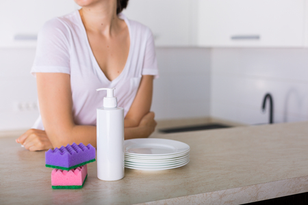 Clean dishes and dishwashing detergent in the kitchen