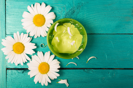 Camomile flowers and organic cosmetics on a bright background