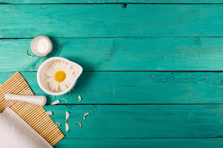 moisturize: Camomile flowers and organic cosmetics on a bright background