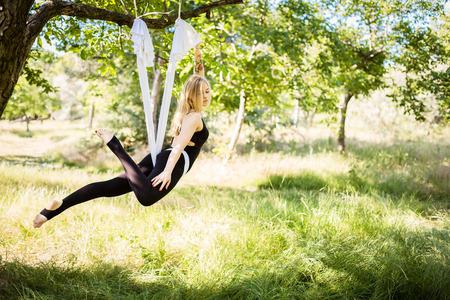 Pretty sporty woman in aerial yoga hammock