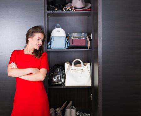 Beautiful woman in red dress standing near her wardrobe