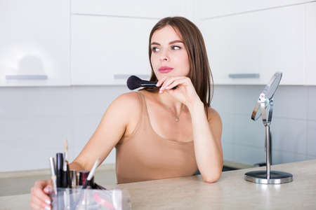 Beautiful woman applying makeup in the morning Stock Photo