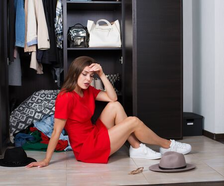 Pretty young woman choosing clothing from the wardrobe Stock Photo