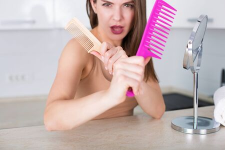 Young pretty woman brushing her hair with pink comb Stock Photo