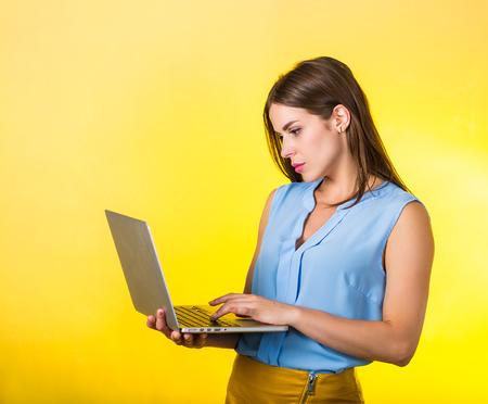 Beautiful stylish young woman holding a laptop