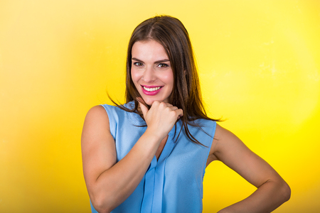Pretty young woman standing against bright background
