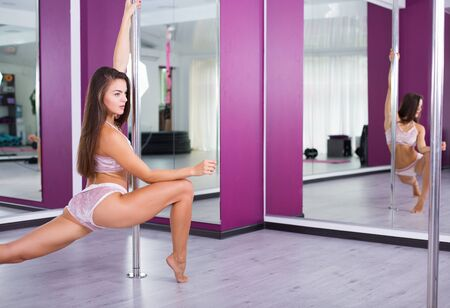woman mirror: Beautiful pole dancer woman dancing in the studio