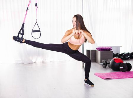 Young beautiful woman working out with straps in the gym
