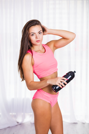 Woman with a water bottle in the fitness studio after workout Stock Photo