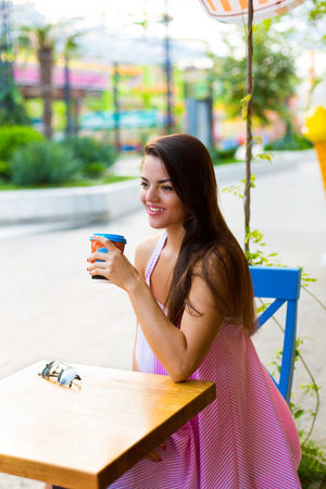 dining table and chairs: Young woman drinking coffee in the street cafe Stock Photo