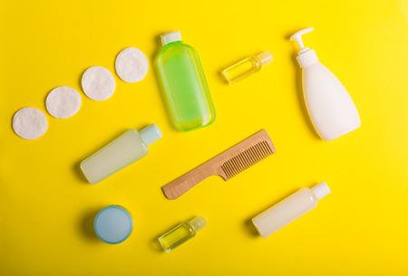 Various generic cosmetics on a yellow background