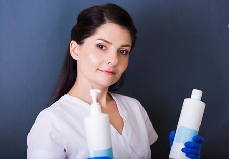 Vrouw cosmetologist houden lotion flessen in een spa salon