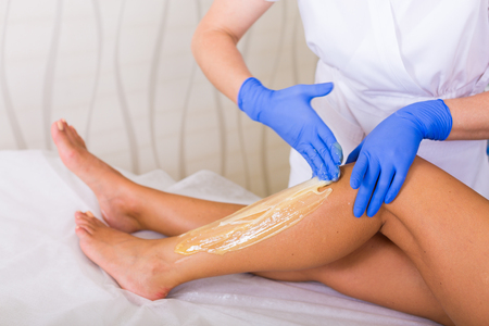 Woman cosmetologist working with sugar paste in a spa salon Stock Photo