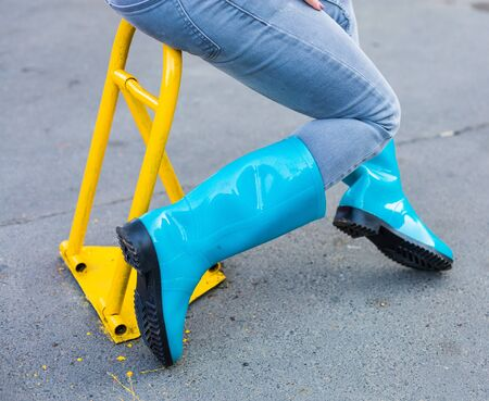 Woman in blue rainboots sitting near a yellow parking stop