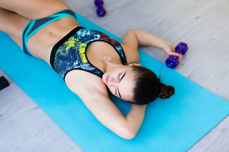 Young woman working out and stretching  in the gym