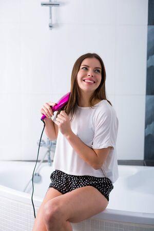 Woman using a hot brush to straighten her hair Stock Photo