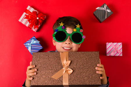 Cute boy surrounded by various Christmas presents Stock Photo