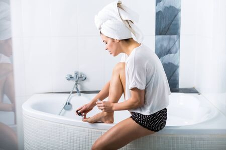 Woman doing her nails in the bathroom early in the morning Stock Photo