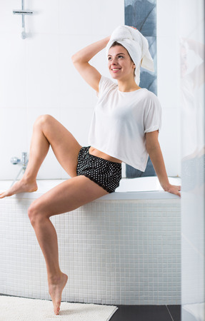 Woman washing her hair in the bathroom early in the morning