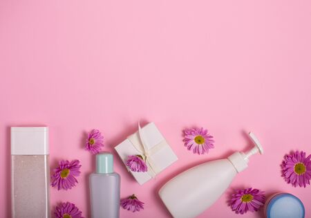 Cosmetics and flowers on a pink background