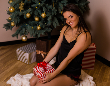 Woman standing by the Christmas tree and holding presents