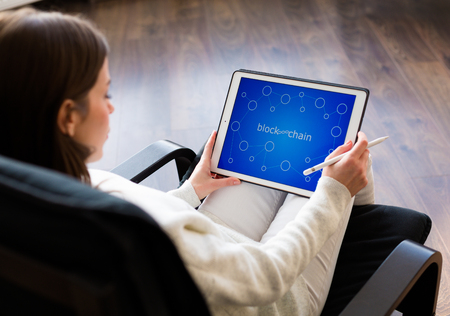 Young woman holding a tablet with cryptocurrency logos Stock Photo