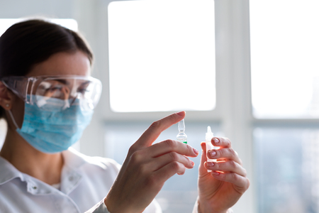 Woman laboratorian holding antibiotics samples and syringe Stock Photo