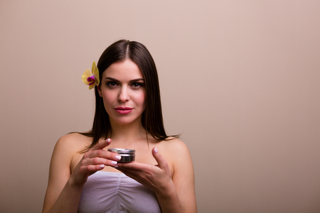 Woman holding a bottle of moisturizing cream