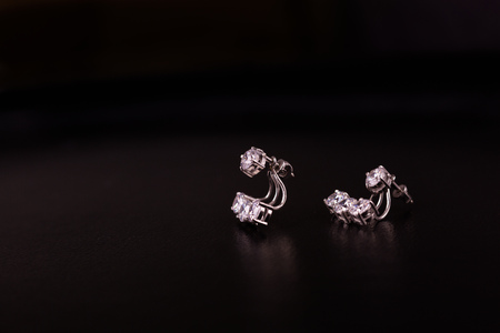Fine silver jewelry on a black background with copy space