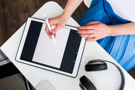 Woman working with a digital tablet shot from above Stock Photo