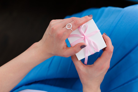 Woman holding a gift box with a pink ribbon