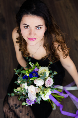 Beautiful young woman holding a lovely bouquet of flowers