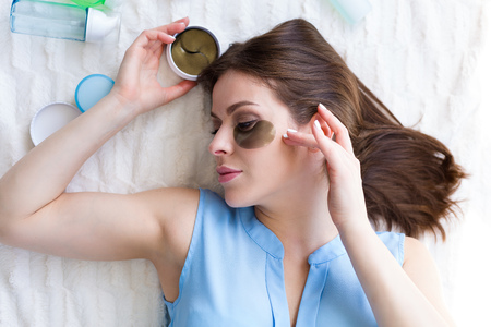 Beautiful young woman applying hydrogel eye patches Stock Photo